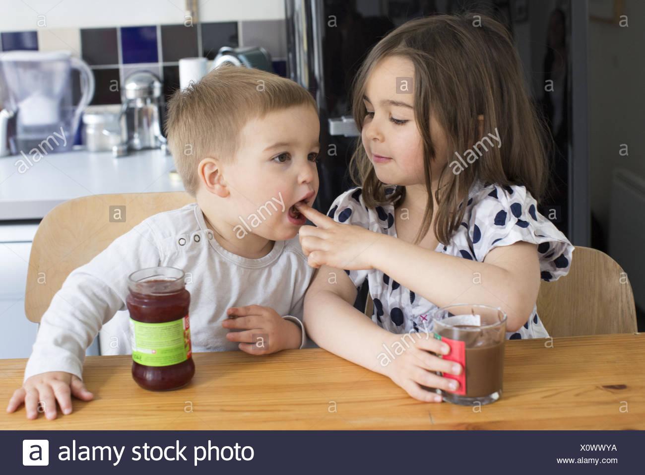Dégustation de jeunes enfants contenu de bocaux avec leurs doigts Photo Stock