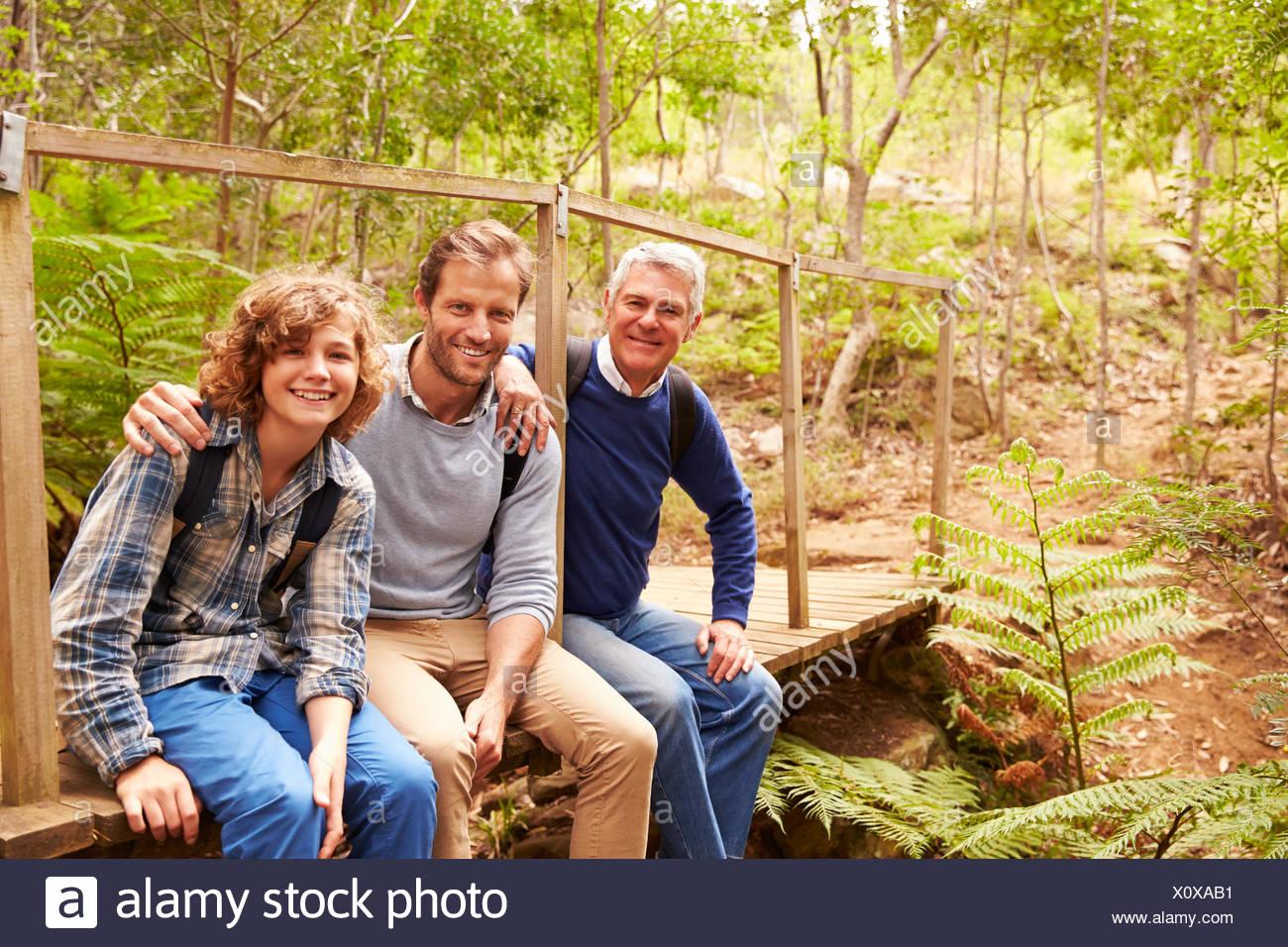 Trois générations d'hommes sur un pont dans une forêt, portrait Photo Stock