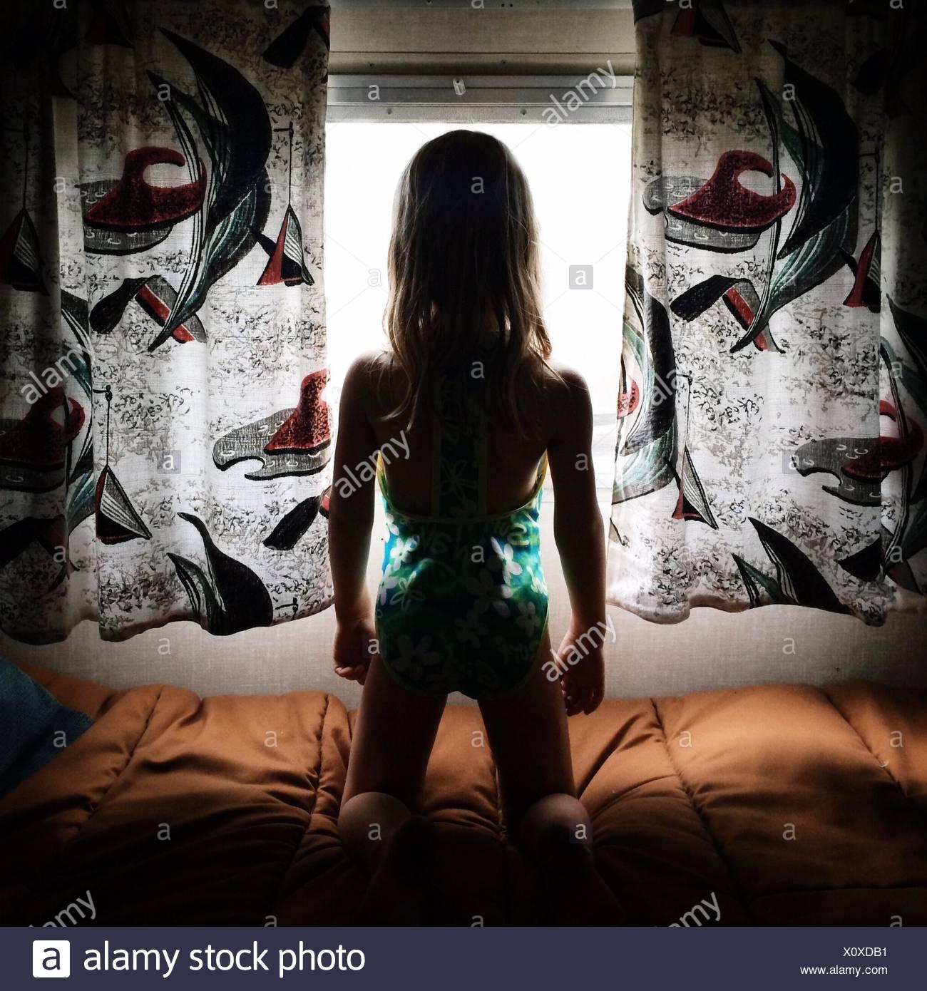 Vue arrière d'une jeune fille à la recherche d'une fenêtre Photo Stock