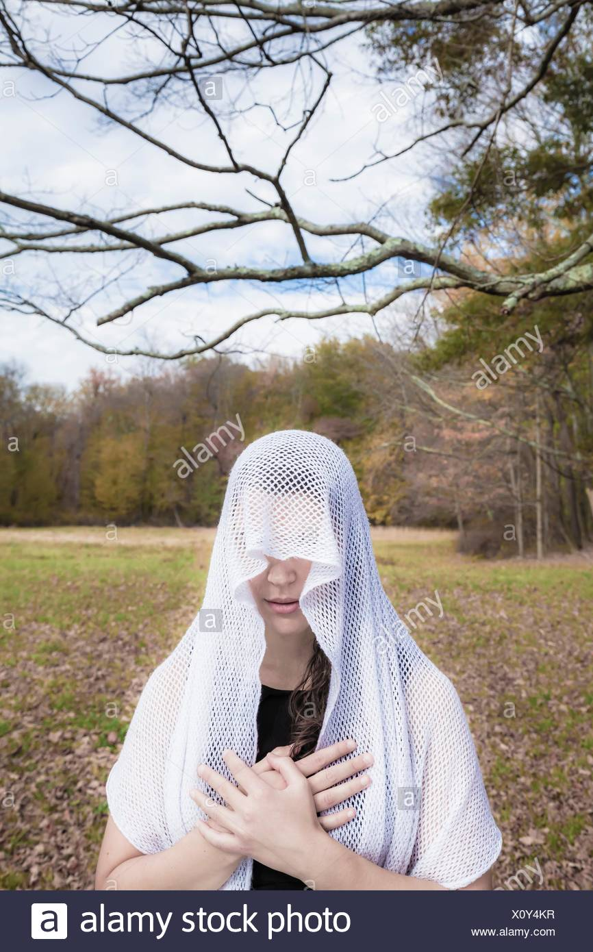 Jeune femme, debout dans un champ ouvert, portant un voile sur sa tête. Banque D'Images