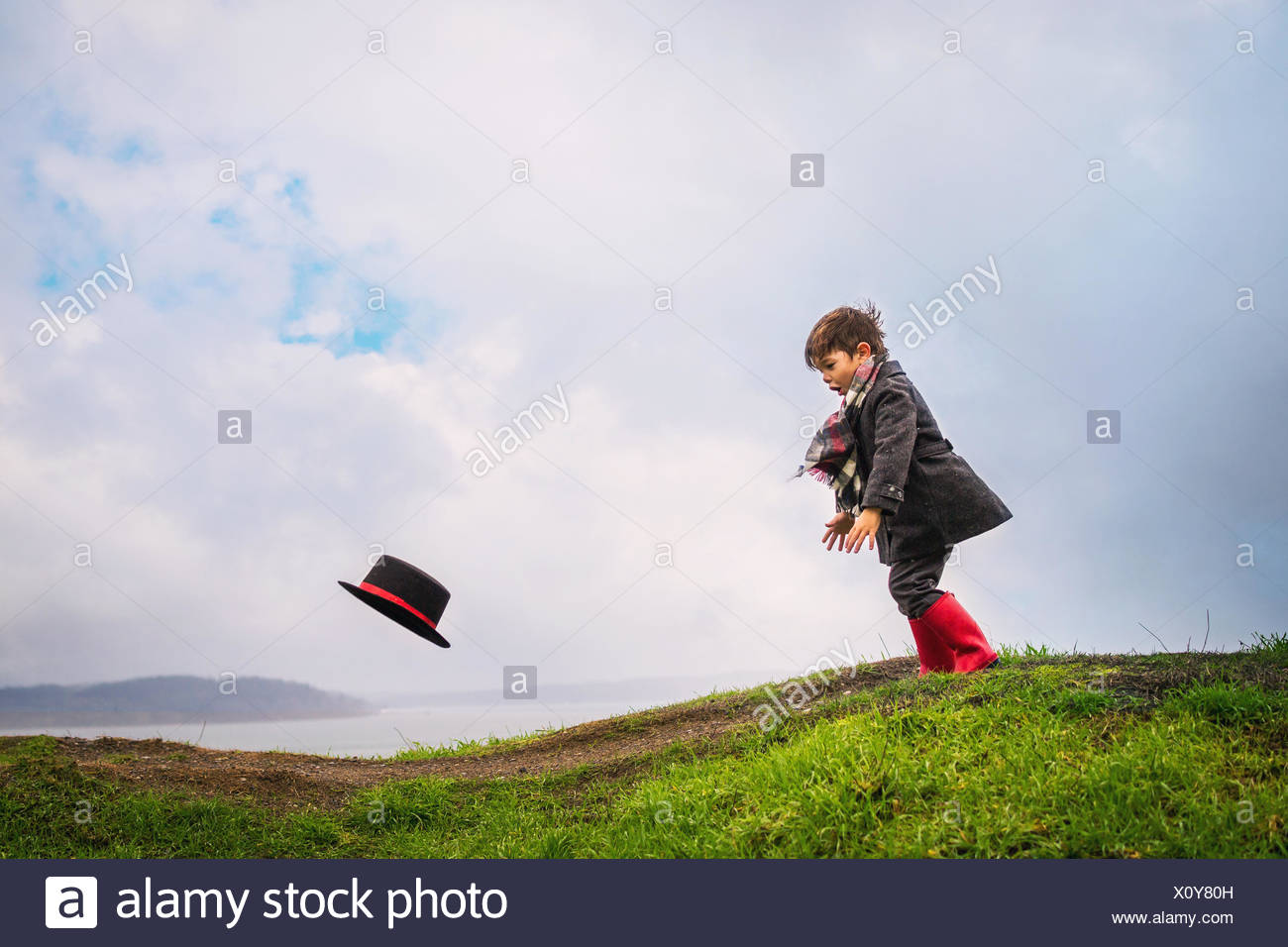Garçon courir après son chapeau souffle loin dans le vent Banque D'Images