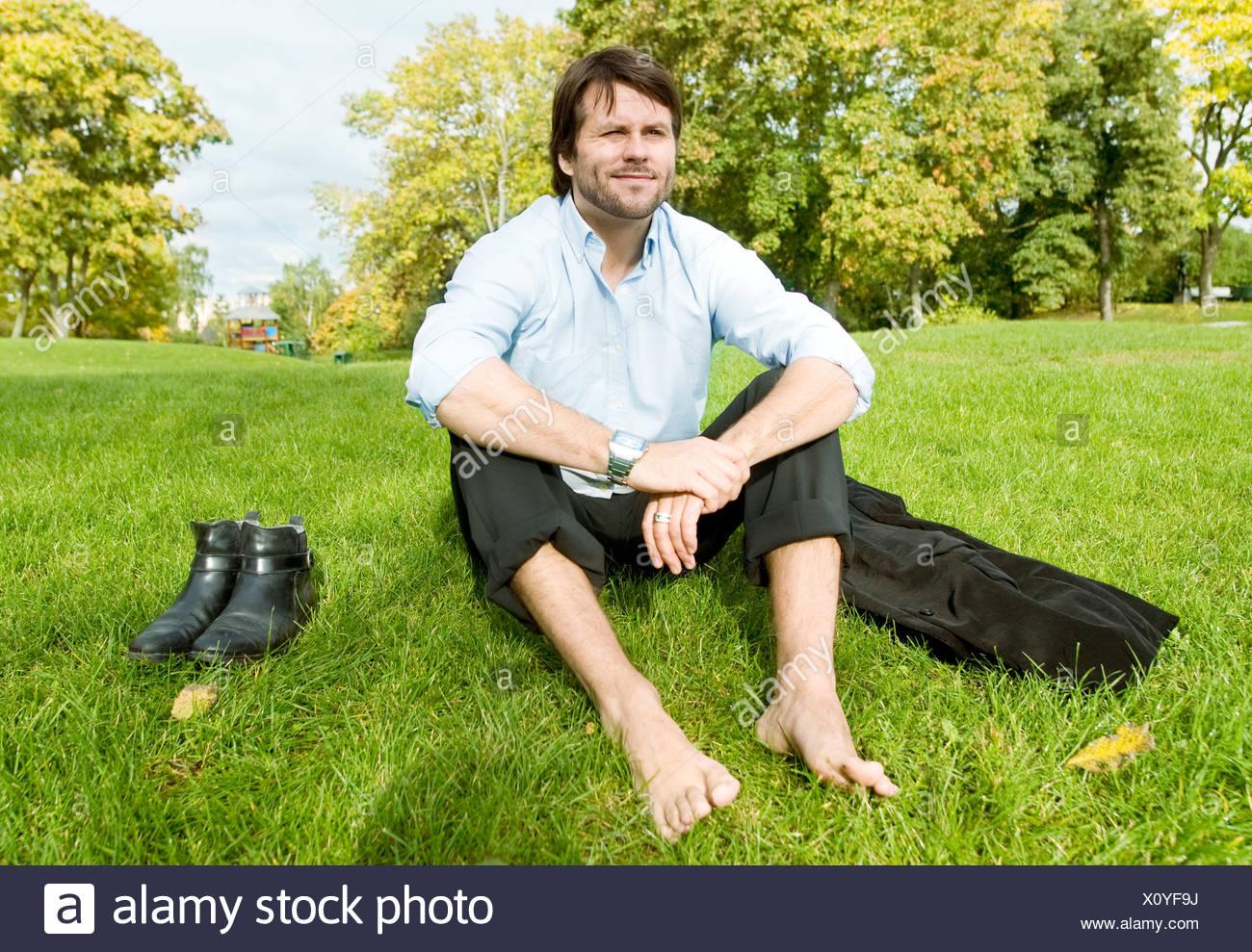 homme assis pied nu sur la pelouse banque d 39 images photo stock 275970622 alamy. Black Bedroom Furniture Sets. Home Design Ideas