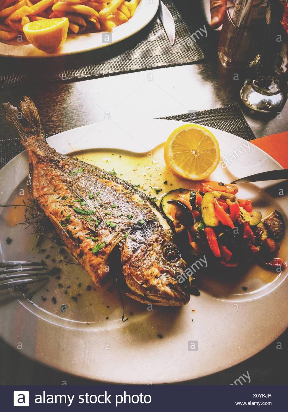 Les poissons grillés avec des légumes grillés Photo Stock