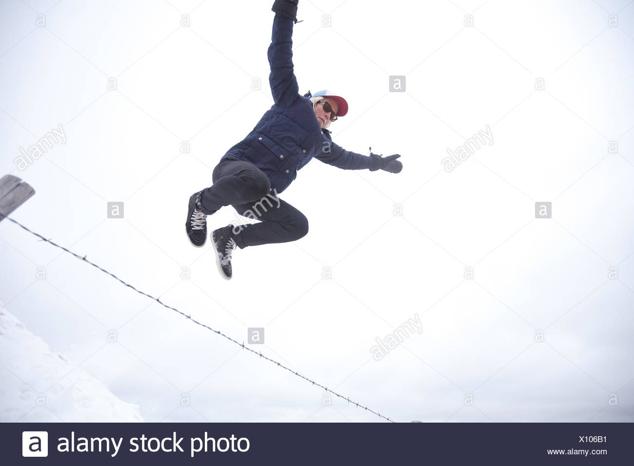 Low angle view of a young man jumping over fence Photo Stock
