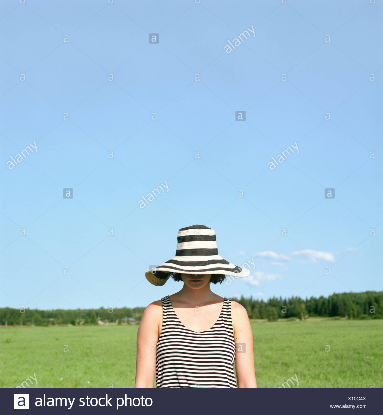 La Finlande, Uusimaa, Lapinjarvi, Woman wearing hat couvrant son visage Photo Stock