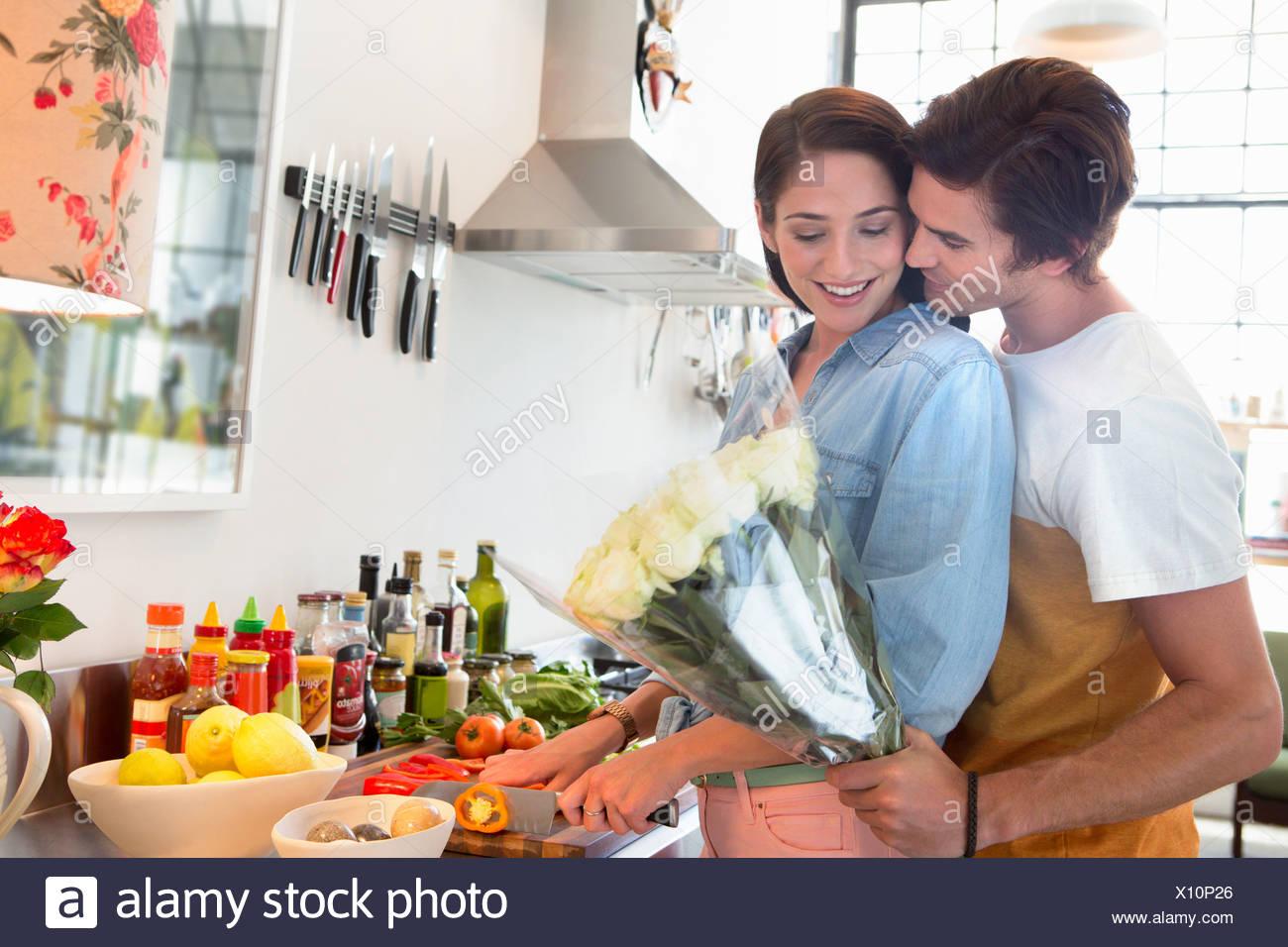 Female friends en cuisine avec bouquet de fleurs Photo Stock
