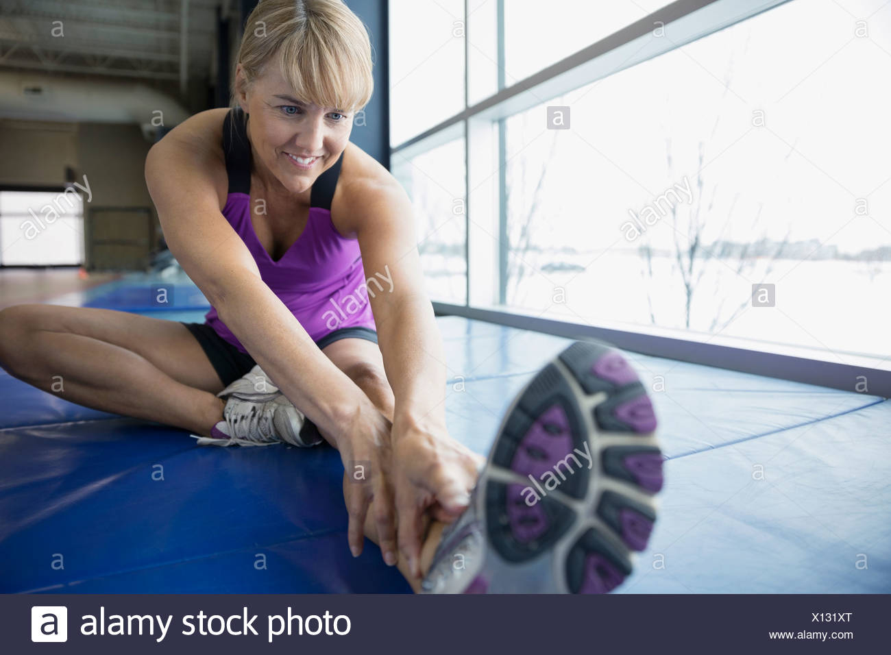 Woman stretching leg at gym Photo Stock