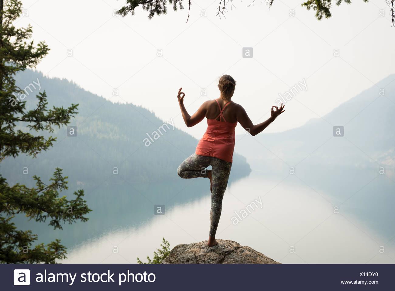 Fit woman en équilibre sur une jambe sur le bord d'un rocher Photo Stock