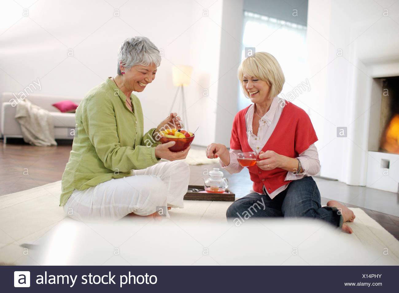 Happy senior femmes prenant le thé et fruits salle de séjour Photo Stock