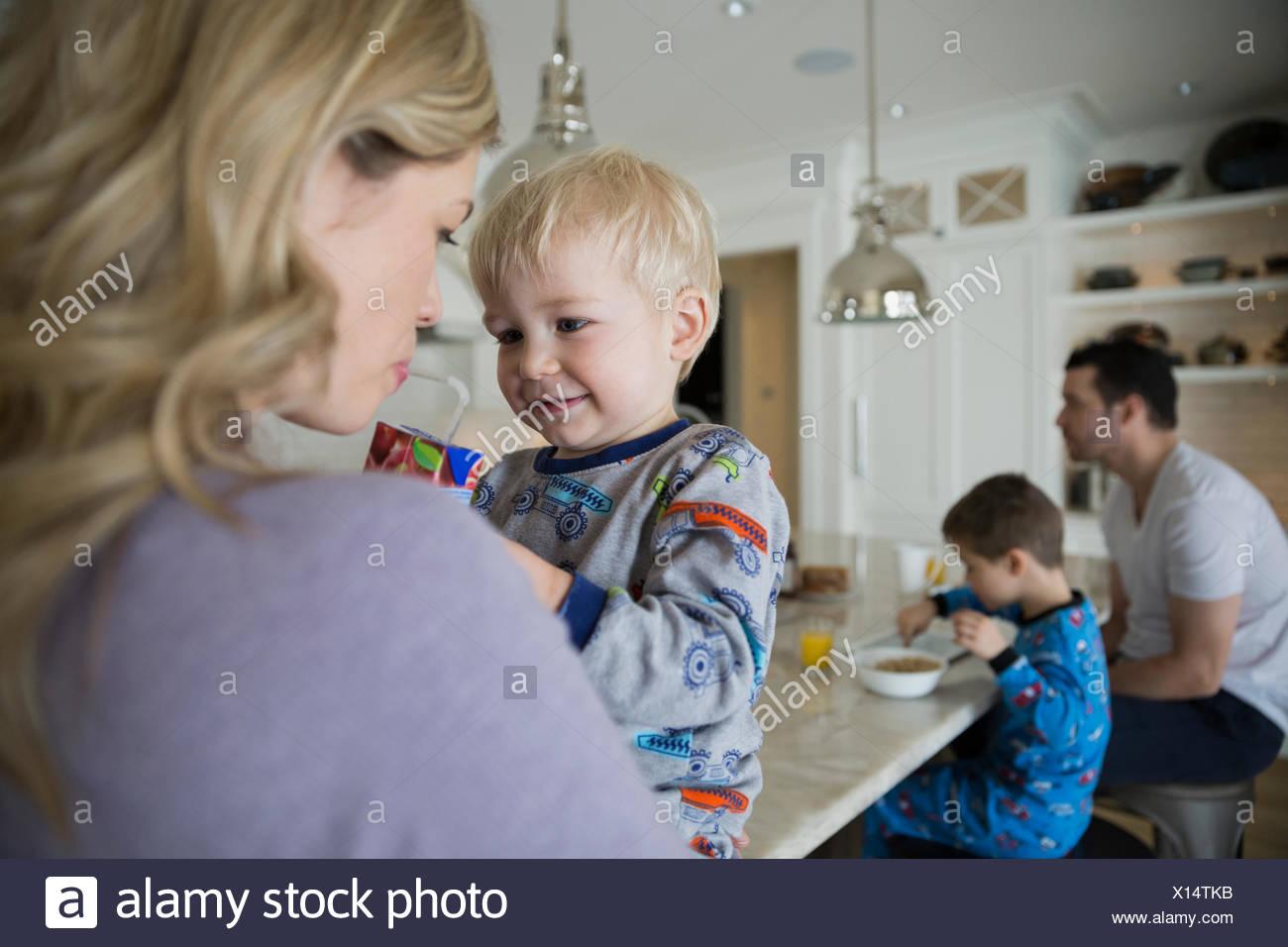 Fils de jus avec mère partage dans la cuisine Photo Stock