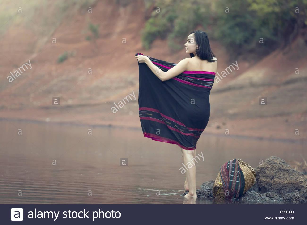 Girl baignant dans creek Banque D'Images