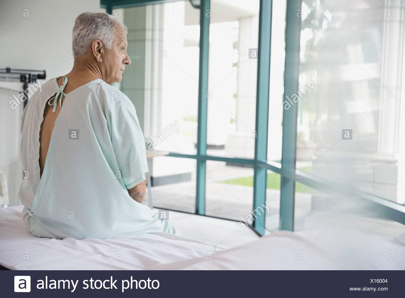 Happy patient assis sur le lit d'hôpital Photo Stock
