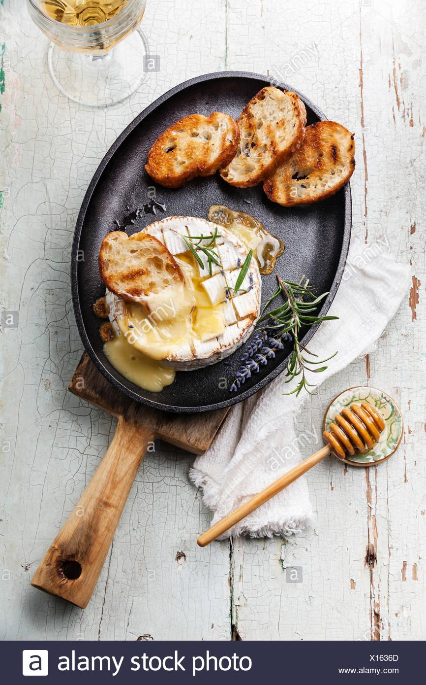 Camembert au four avec du pain grillé sur le poêle en fonte Photo Stock