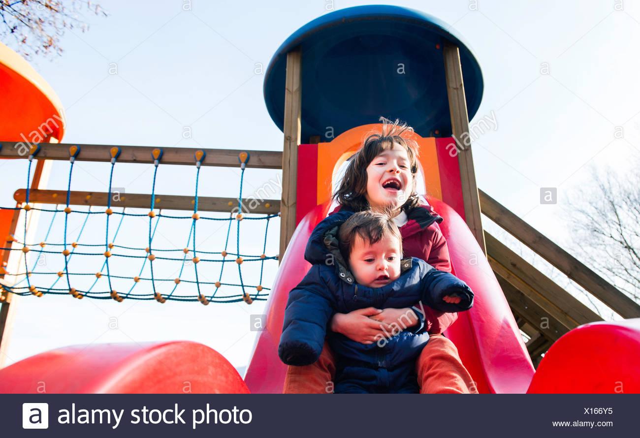 Garçon et frère bébé glissant sur aire de glisse Photo Stock