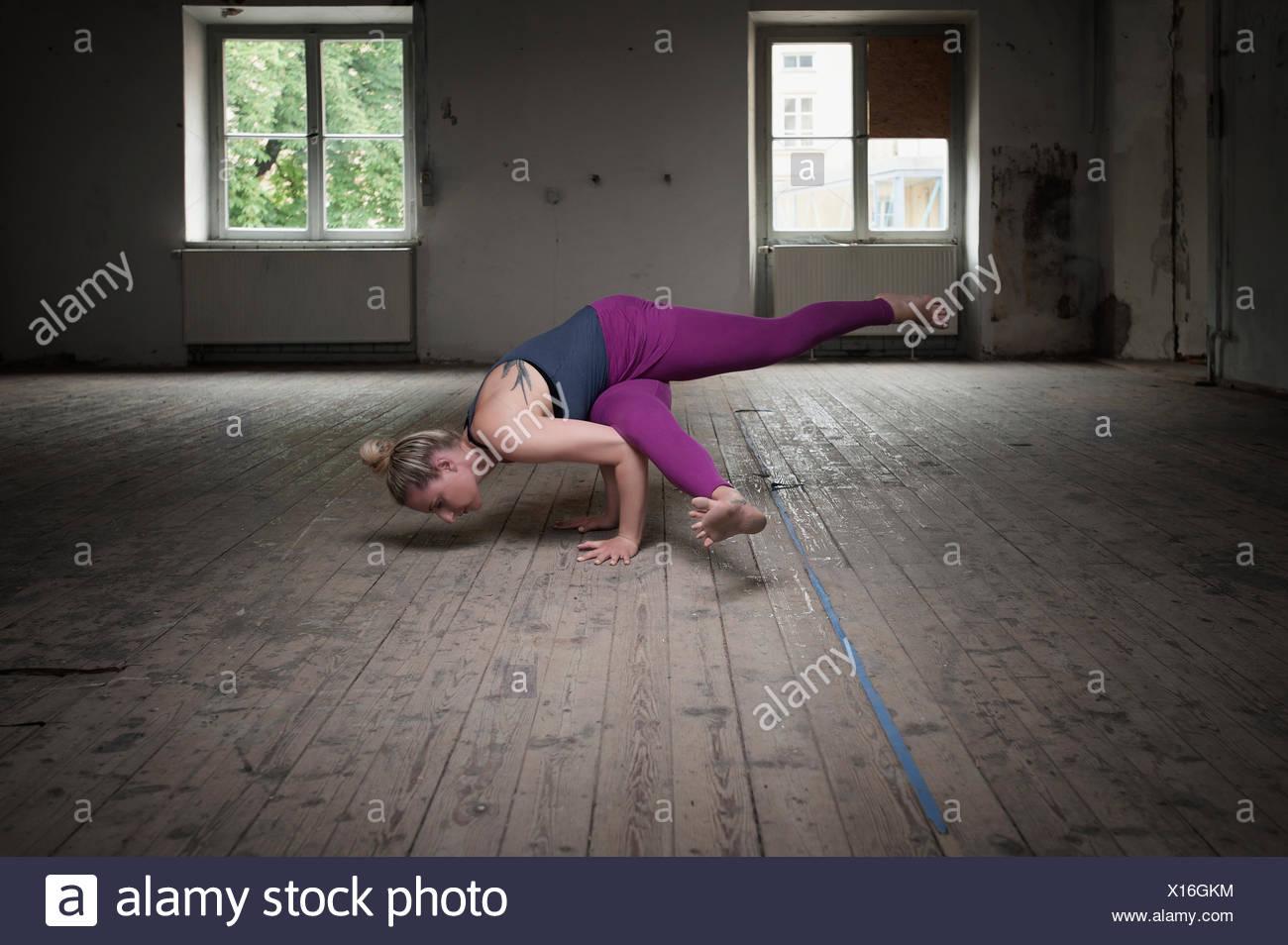 Mid adult woman practicing Eka pada koundinyasana je pose dans un studio de yoga, Munich, Bavière, Allemagne Banque D'Images
