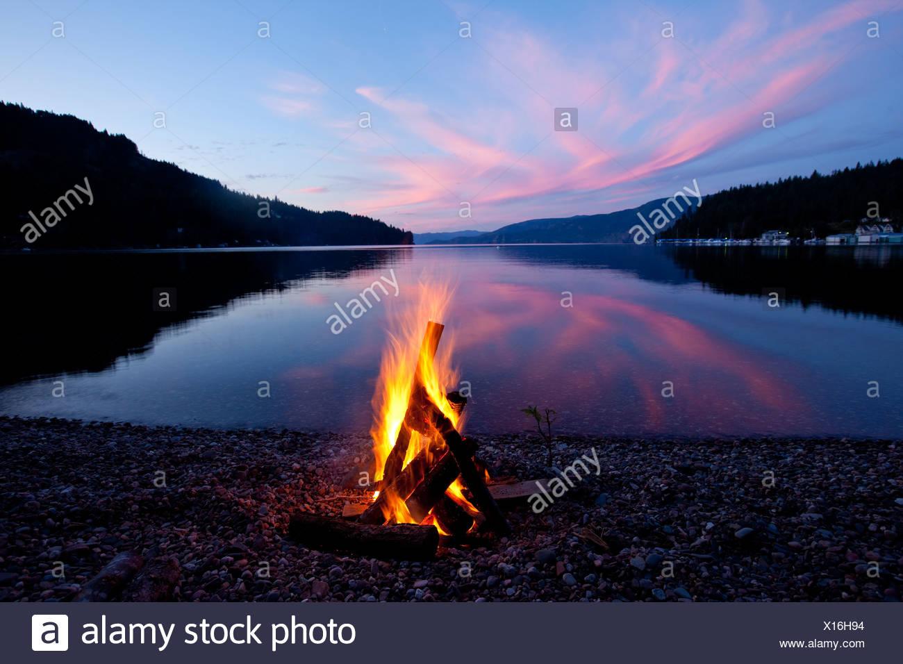 Feu de camp avec coucher du Soleil reflété sur le lac en Idaho. Photo Stock