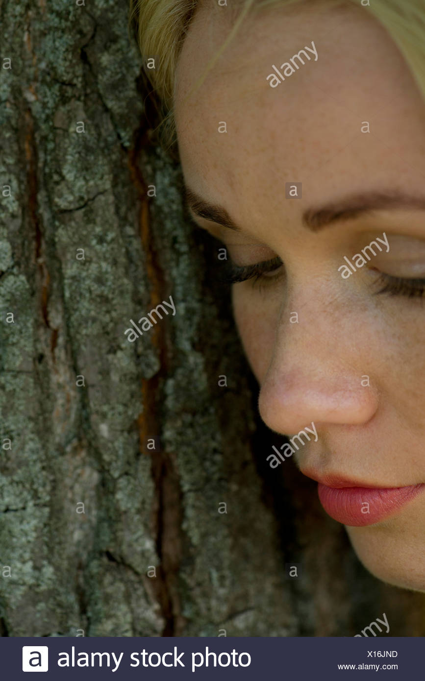Young woman leaning against tree trunk, regardant tristement Photo Stock