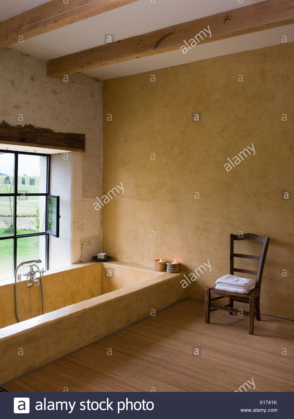 chaise en bois simple à côté d'une baignoire en marbre encastrée en