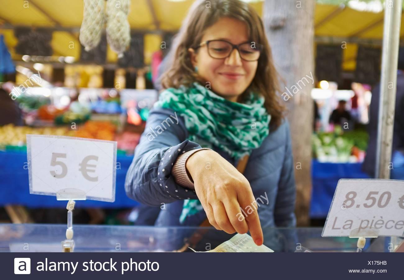 Jeune femme achat de biens at market stall Photo Stock