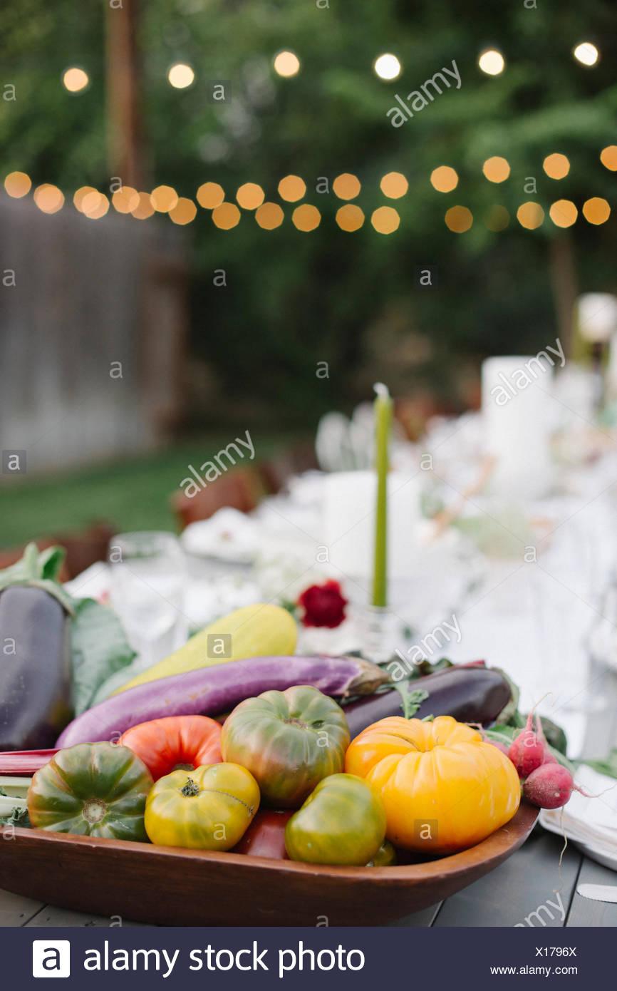 Longue table avec des assiettes et des verres, de l'alimentation et des boissons dans un jardin, un bol de légumes dans l'avant-plan. Photo Stock