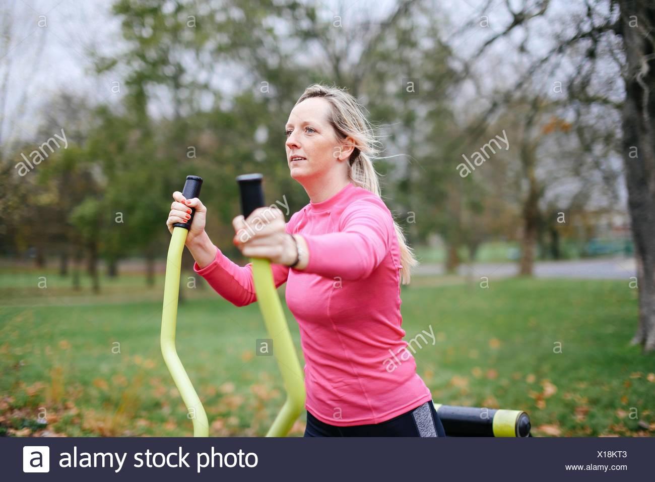 Jeune femme formation sur machine d'exercice dans le parc Photo Stock