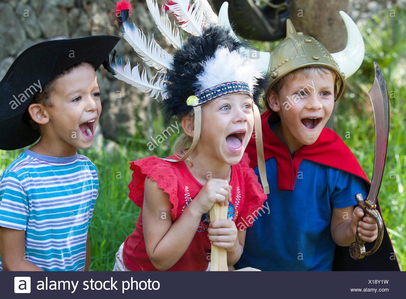 Trois enfants portant des costumés, jouant dans le parc Photo Stock
