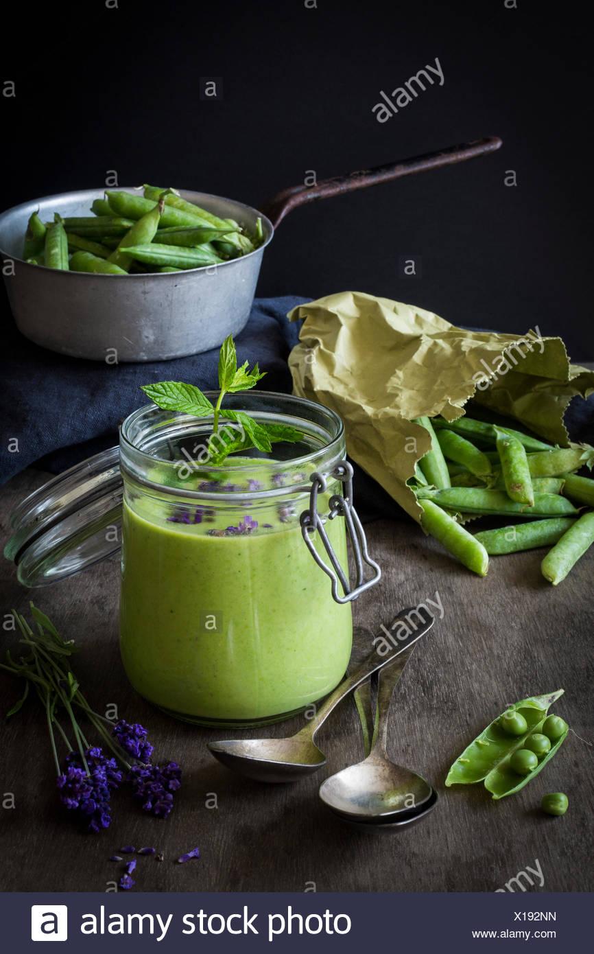 Gaspacho vert en pot avec des petits pois et de lavande sur table en bois avec une passoire et cuillères vintage Banque D'Images