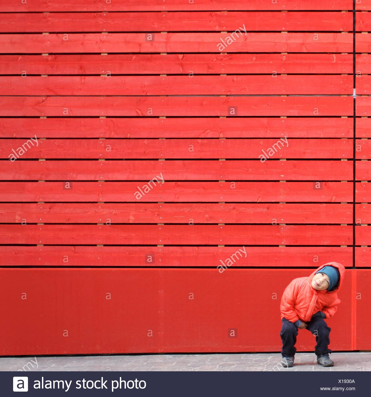 Garçon en rouge, jouer en face d'un mur rouge Photo Stock