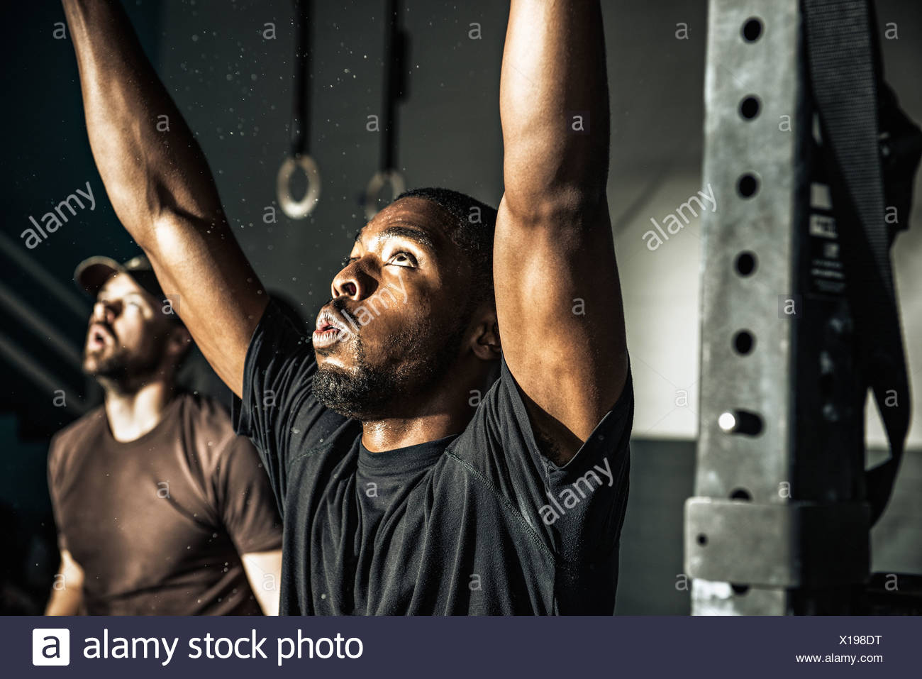 Close up of young man training on exercise bar in gymnasium Photo Stock
