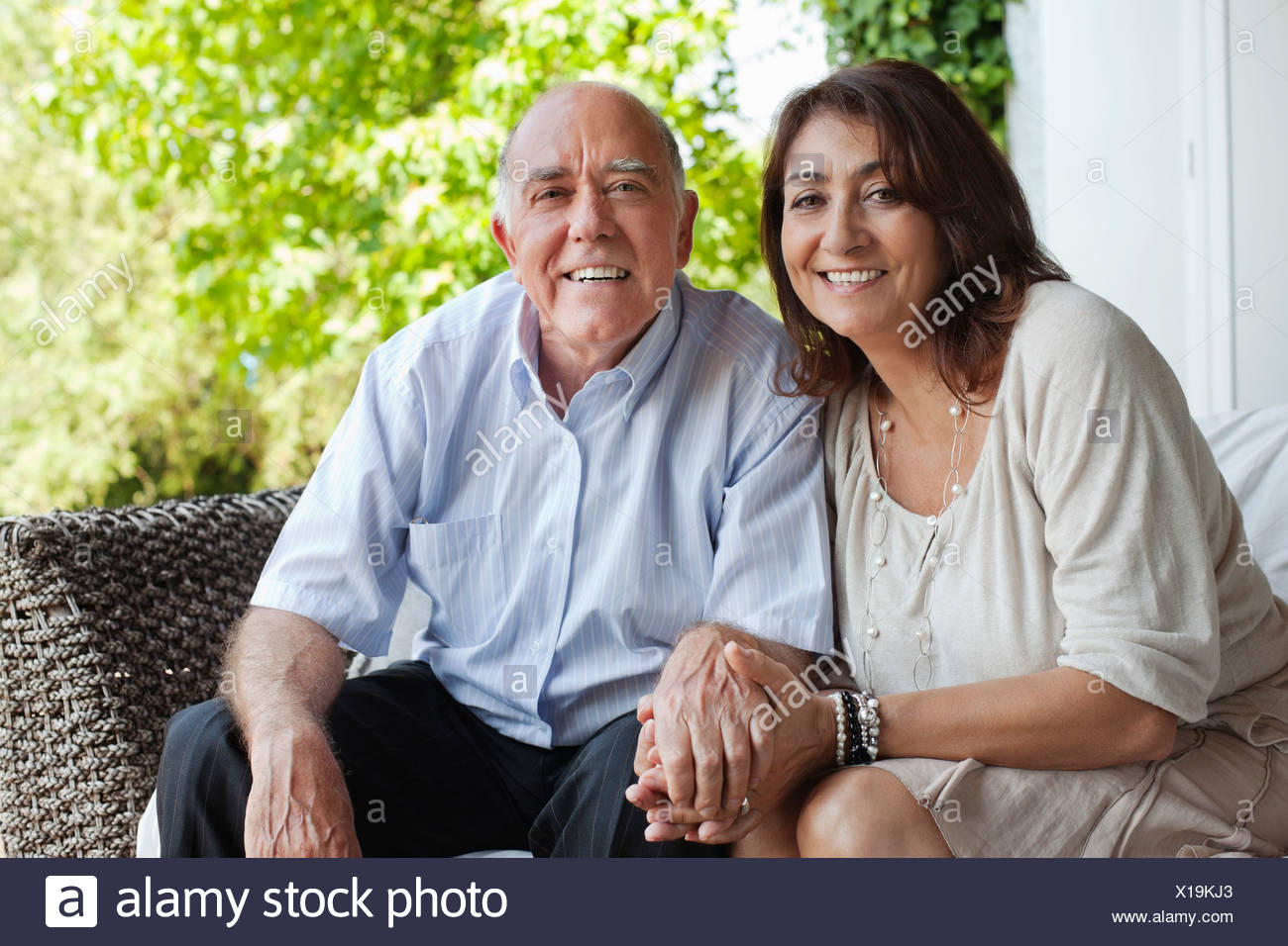 Couple holding hands on patio Photo Stock
