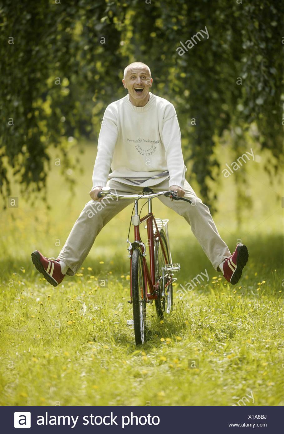 Hauts beim Radfahren auf Wiese, lacht (modèle récent) Photo Stock