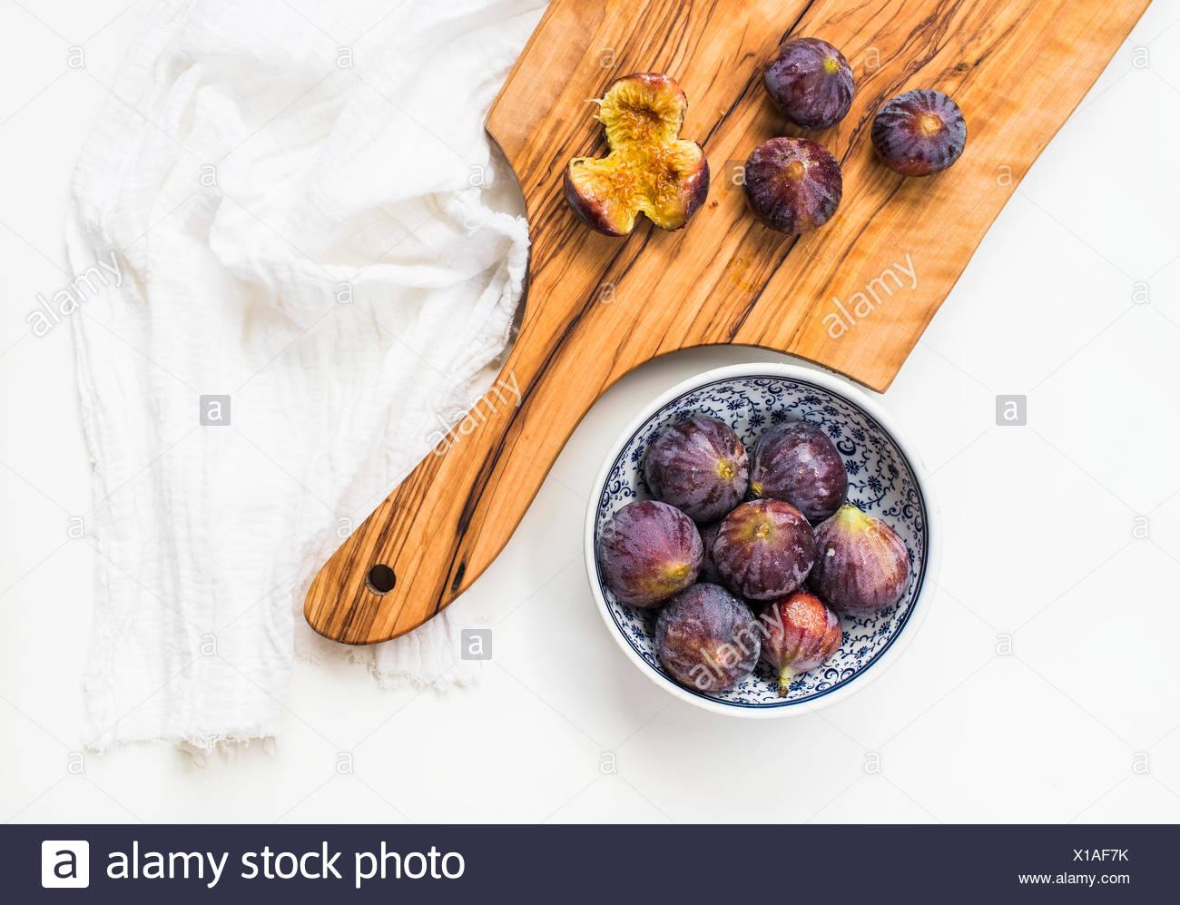 Figues fraîches en bleu Bol en céramique à motifs et sur bois d'olive sur fond blanc, vue du dessus Photo Stock