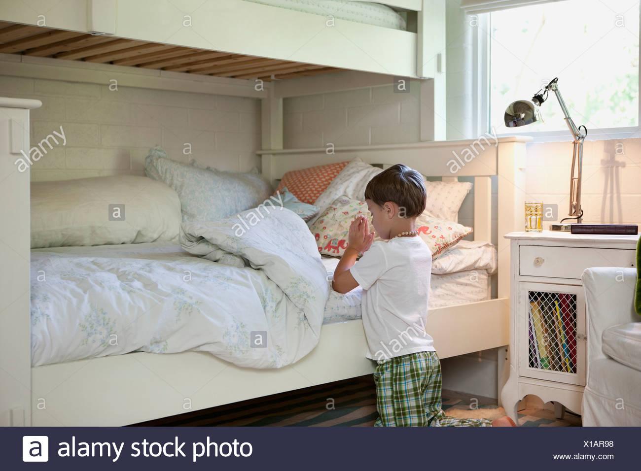 Garçon priant avant lit Photo Stock