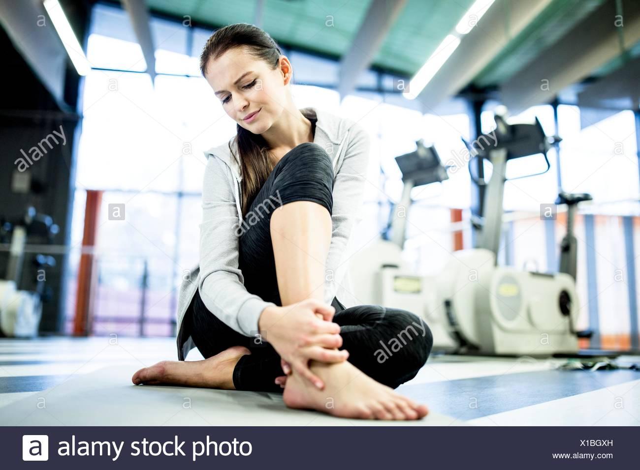Parution de la propriété. Parution du modèle. Jeune femme masser tout en ayant la cheville cheville douleur dans la salle de sport. Photo Stock