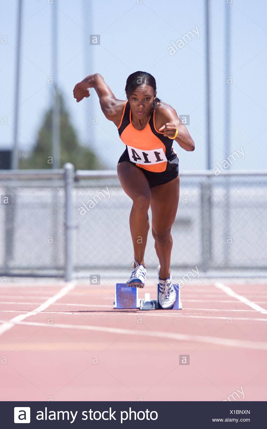 Coureuse africaine laissant bloc de départ Photo Stock
