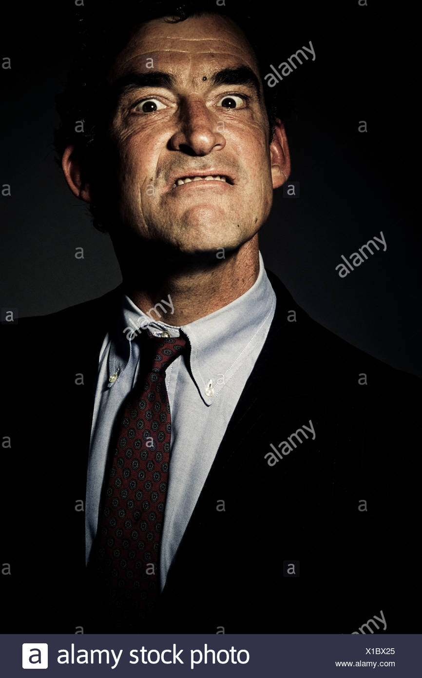 L'angle faible, Close up, tête et épaules vue d'un homme mûr dans un costume avec une expression de colère sur son visage (studio shot Photo Stock