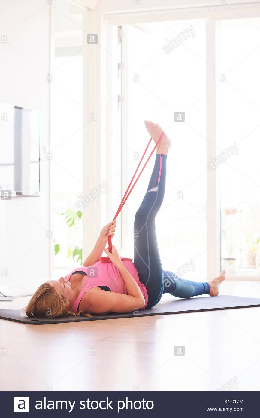 Jeune femme enceinte faire de l'exercice dans la salle de séjour augmenter sa jambe Banque D'Images