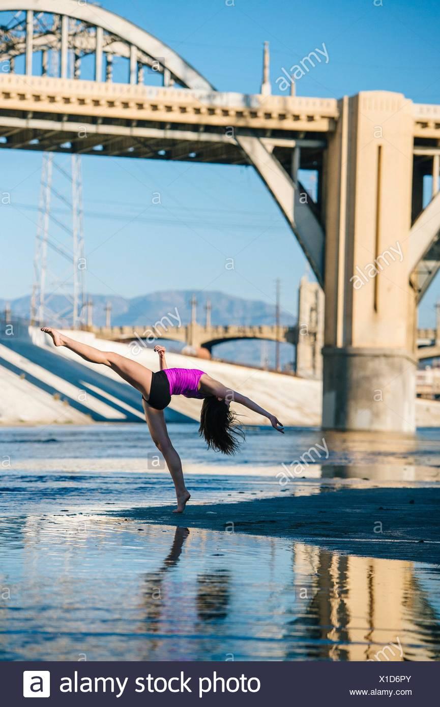Vue latérale du danseur, jambe soulevée, penché au-dessus de l'arrière à l'avant du pont, Los Angeles, Californie, USA Photo Stock