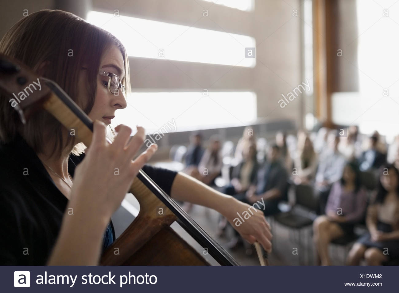 Le violoncelliste femelle pour l'auditoire de la scène à l'auditorium Photo Stock