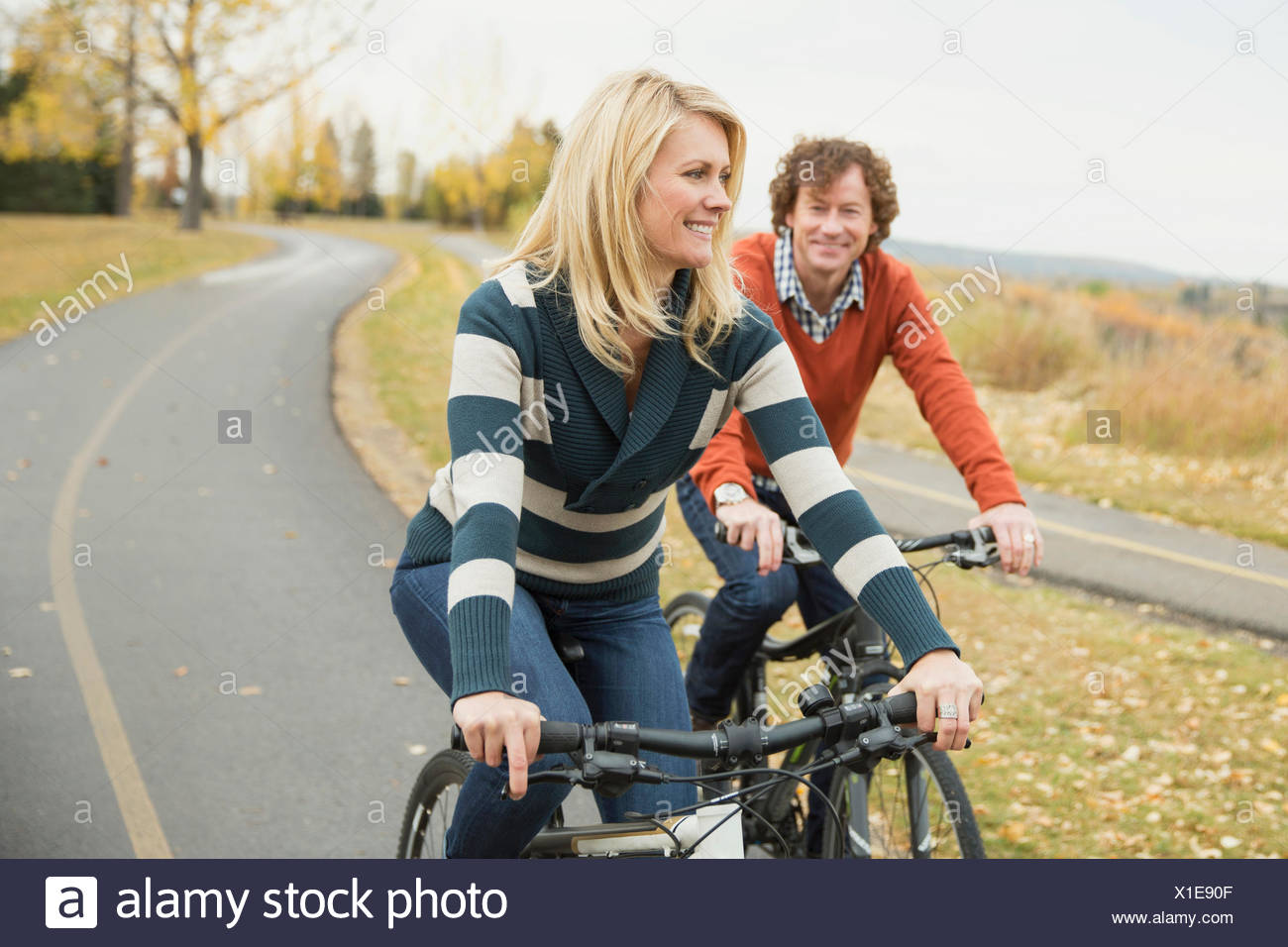 Mature couple riding bicycles sur pathway Photo Stock