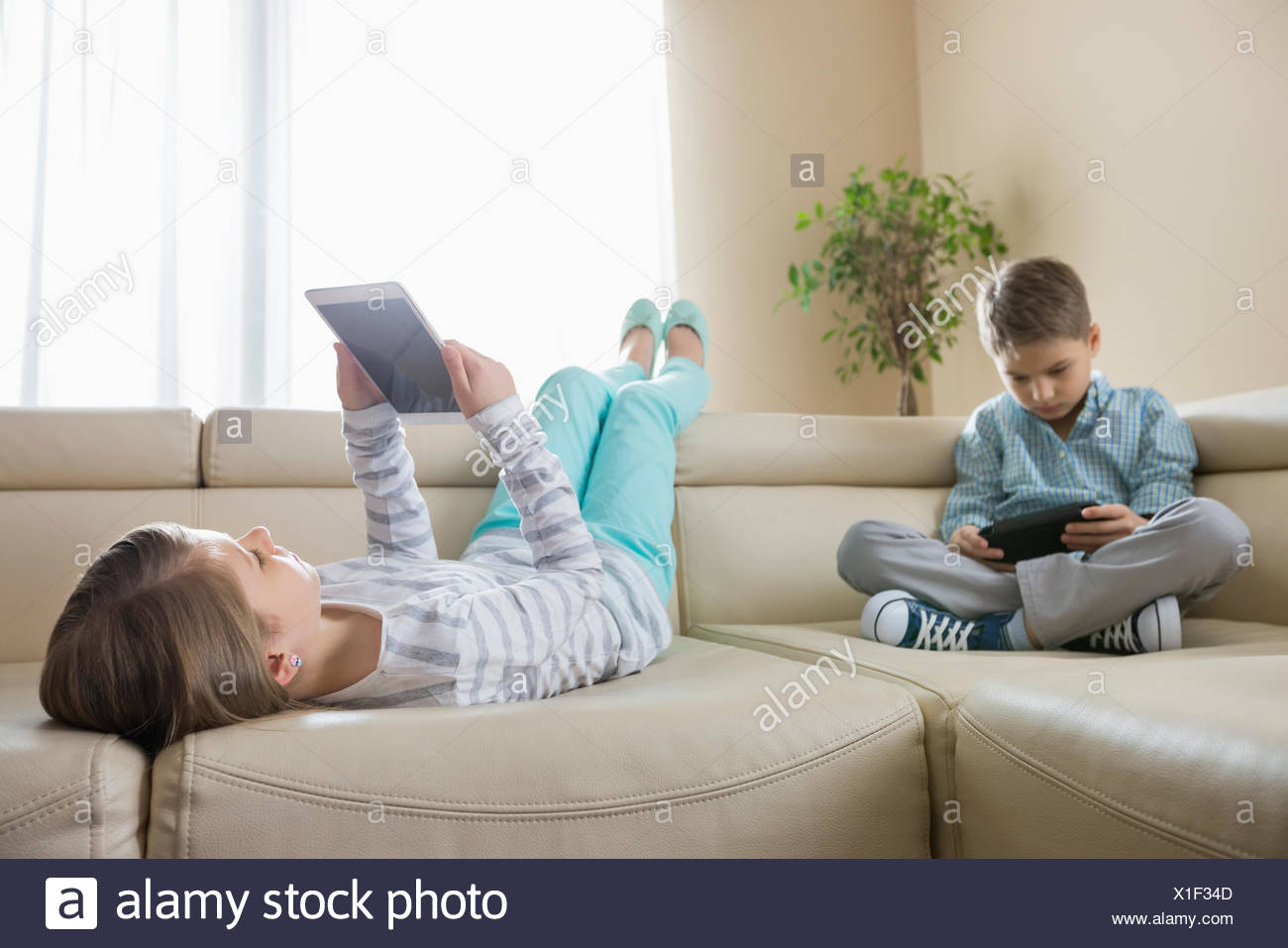Frères et sœurs à l'aide de technologies sur le canapé à la maison Photo Stock