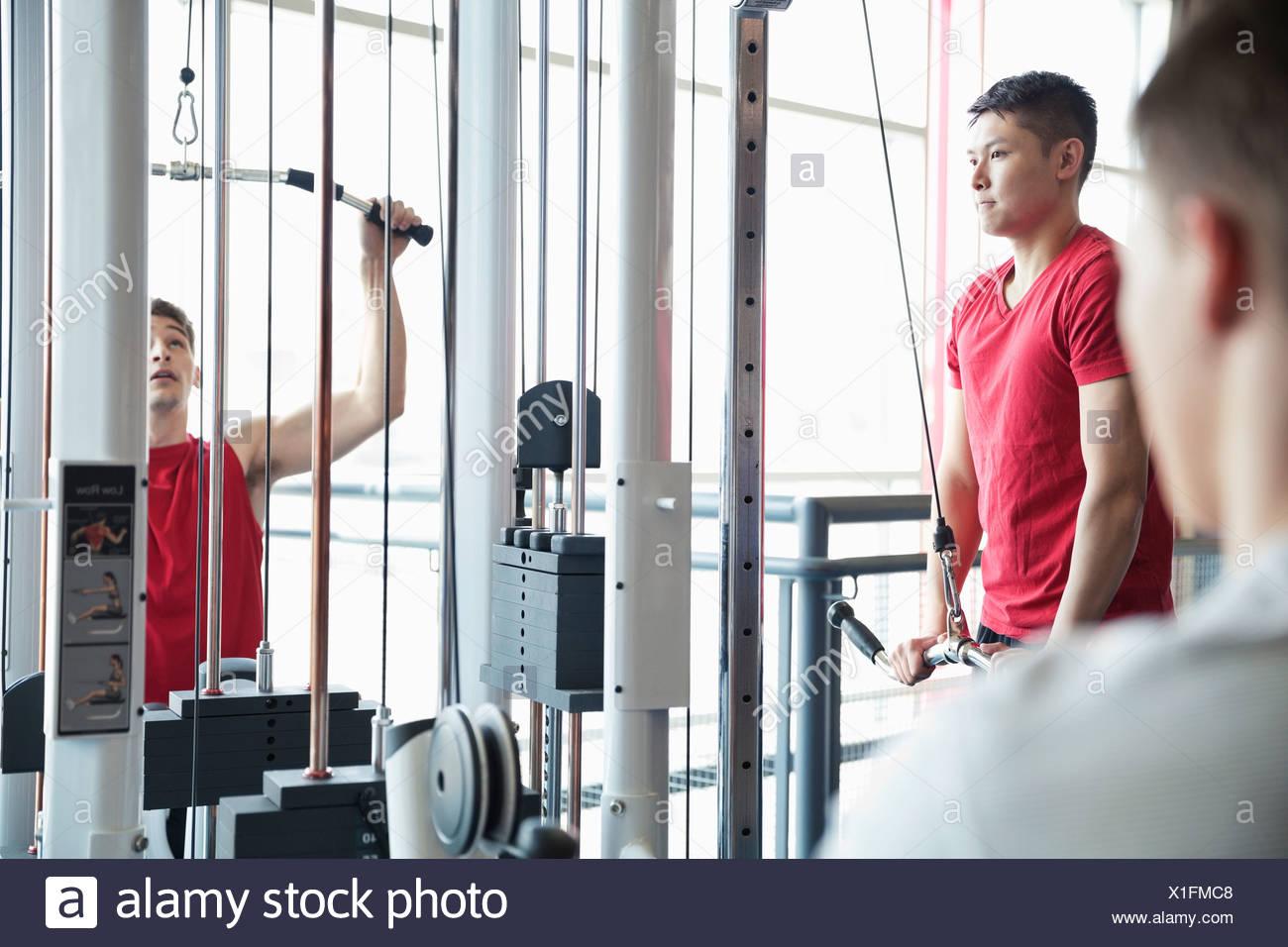 Les hommes à l'aide d'appareils de musculation en centre de remise en forme Photo Stock