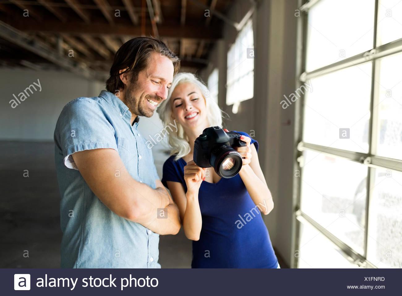 La femme et l'homme à la recherche de photos dans un appareil photo numérique Photo Stock