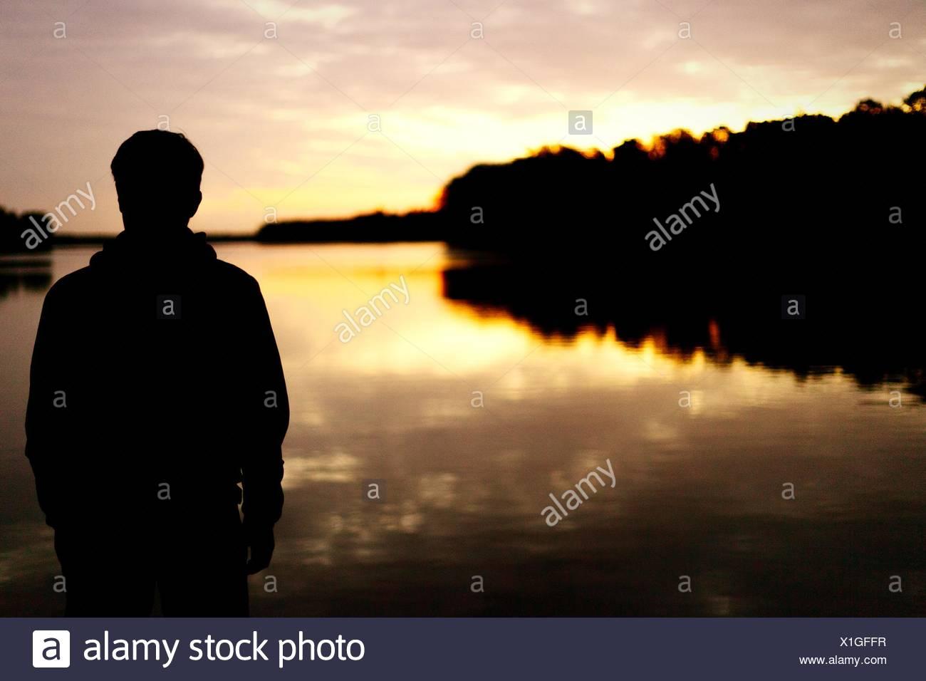 Vue arrière de l'ossature Homme debout en face du lac au coucher du soleil Photo Stock