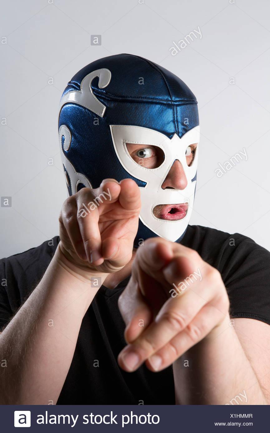 Un homme portant un masque de catch Lucha Libre et gesticulant bizarrement avec ses mains Photo Stock