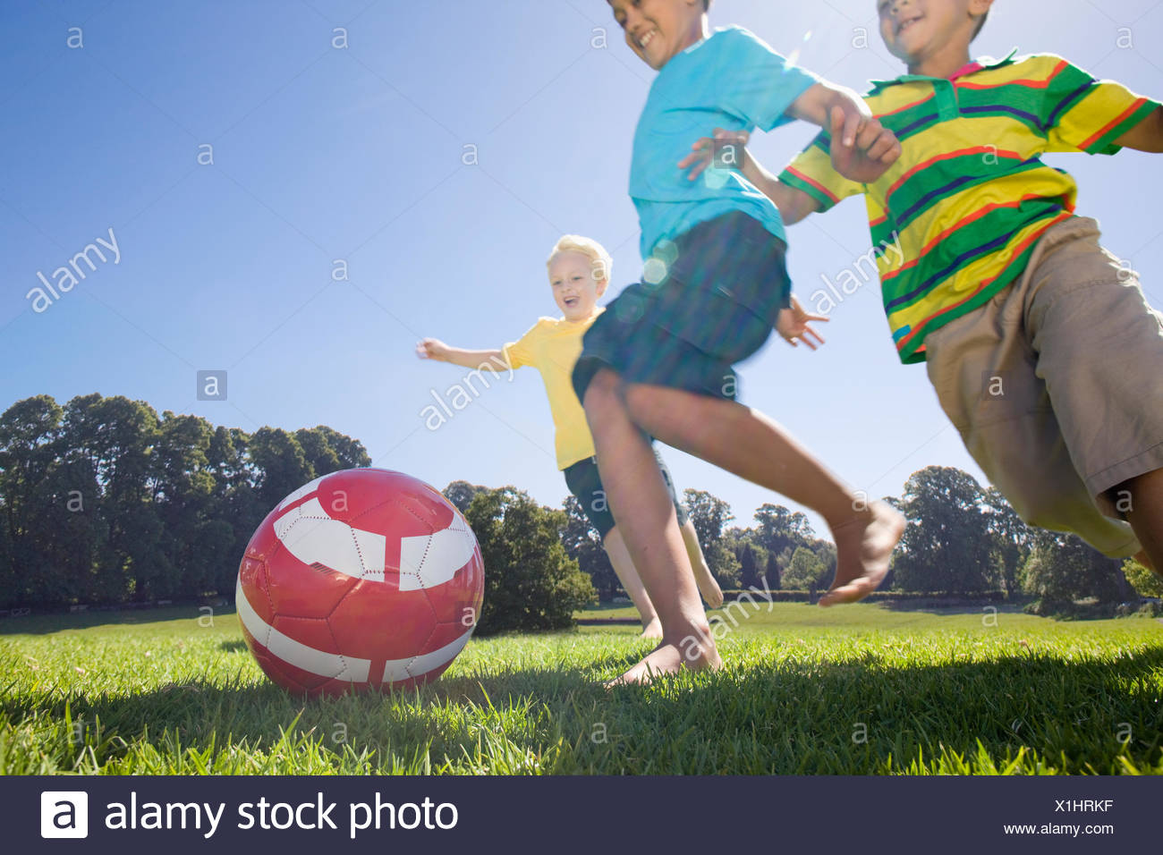 Smiling boys playing soccer in park Photo Stock