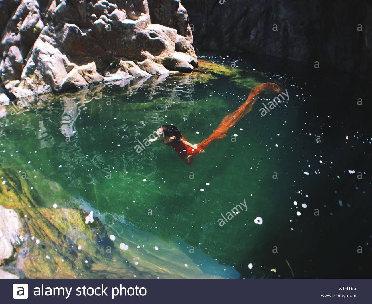 Femme en robe rouge sous l'eau Photo Stock