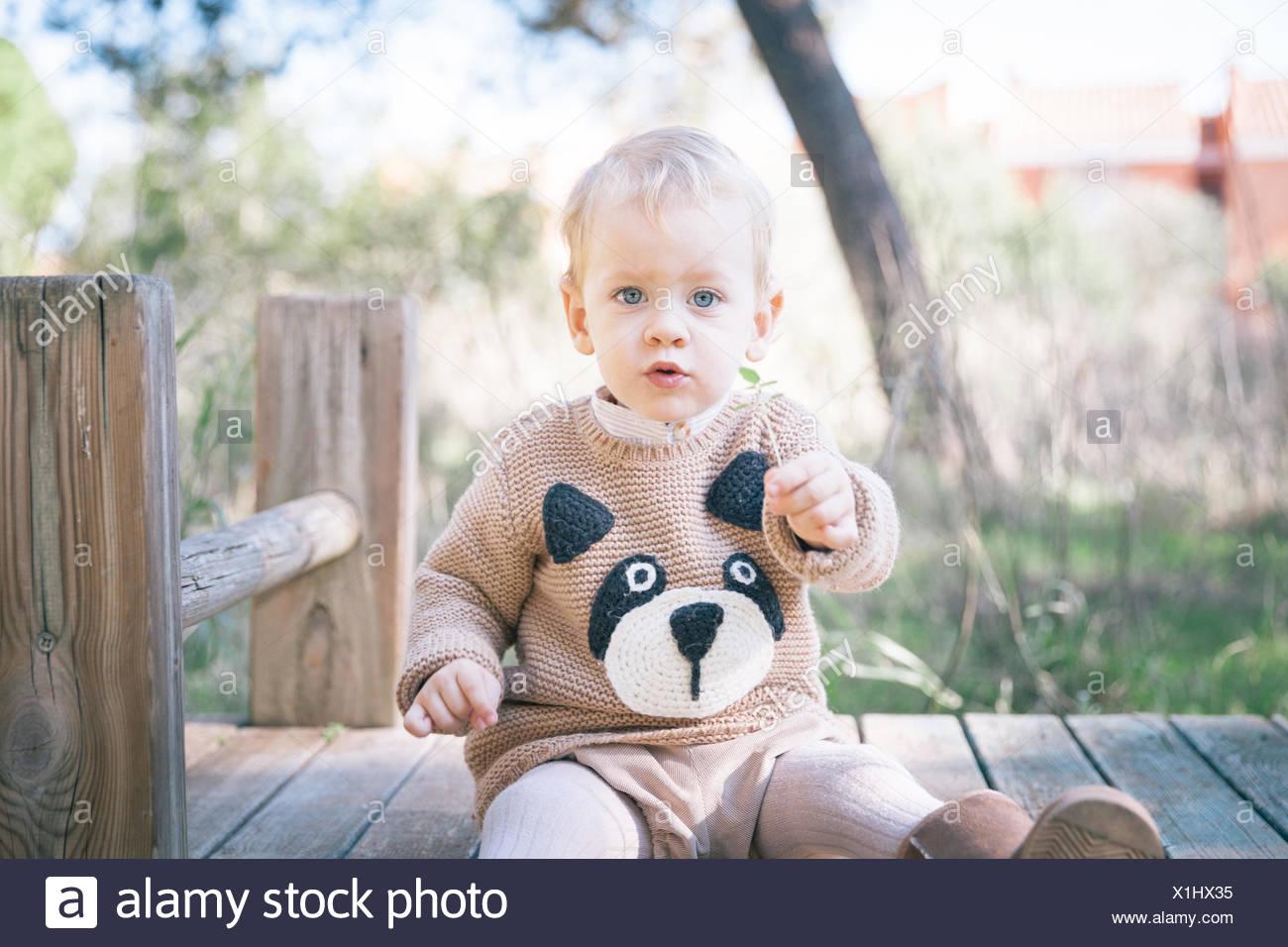 Garçon assis sur une structure construite en jeu pour enfants Banque D'Images