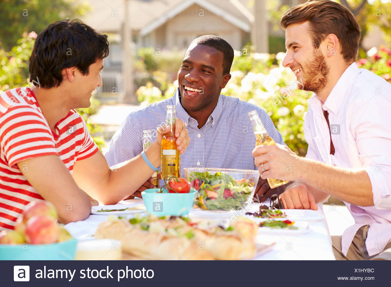 Trois Amis Enjoying Meal At Outdoor Party Photo Stock