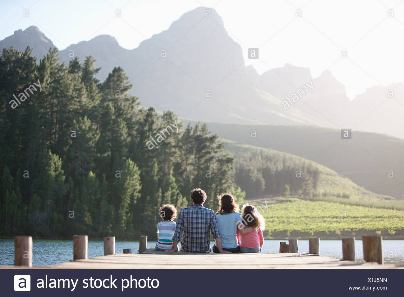 Family sitting on lake dock Photo Stock